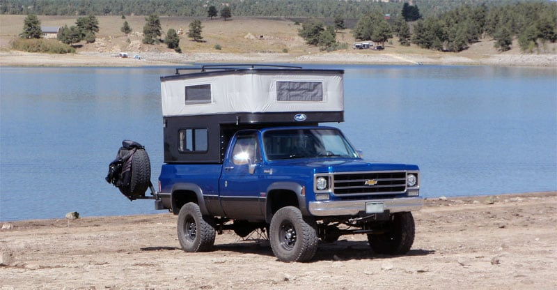 Camper Backed Up To Lake Relaxing