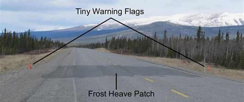 Frost Heave With Orange Warning Flags