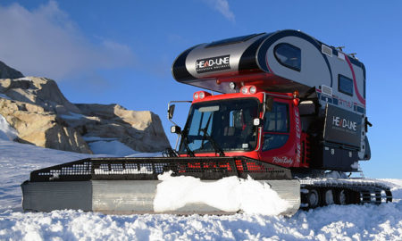 Snowcat truck camper pushing snow