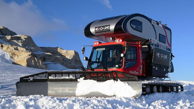 Snowcat truck camper pushing snow