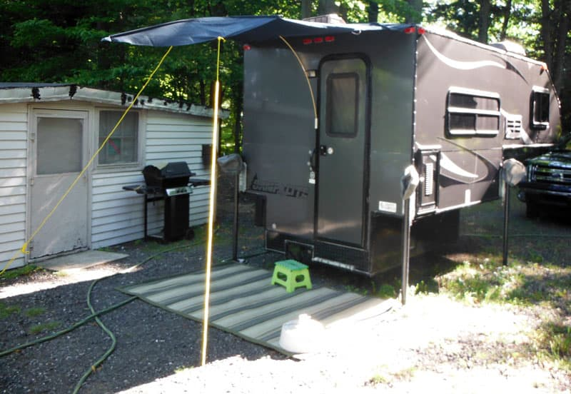 Awning attached to camper roof with two brackets