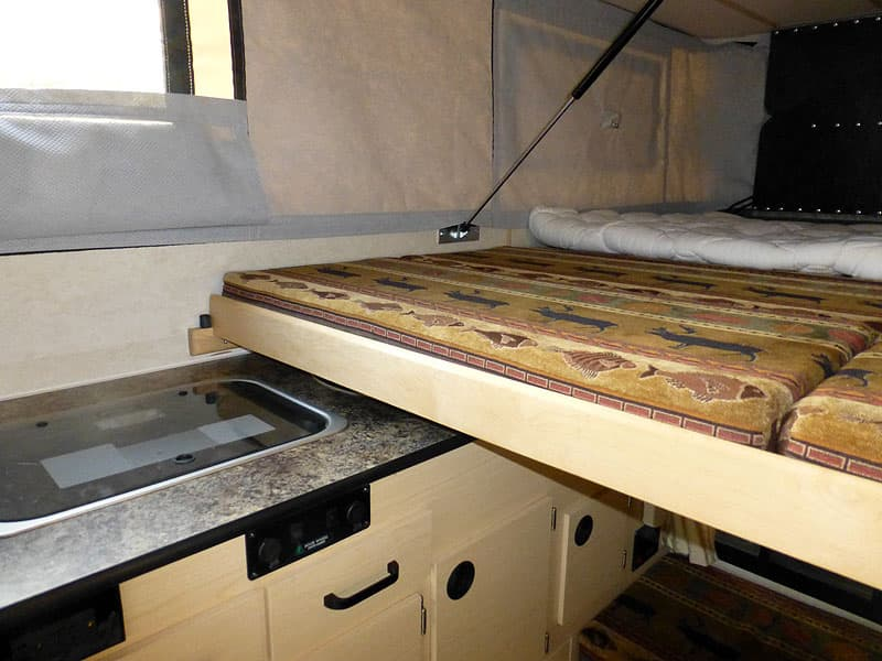 King bed being made in Four Wheel Camper