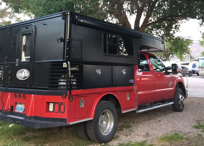 Black truck camper and red truck