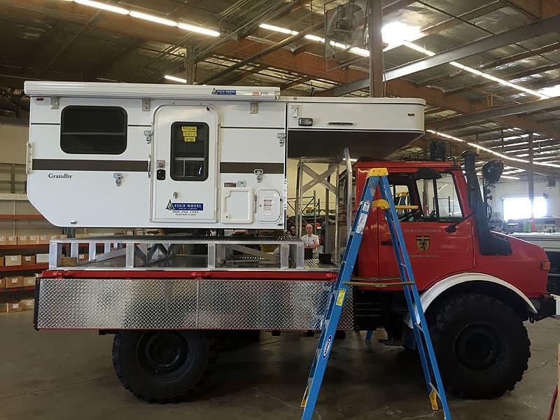Unimog camper loaded on truck platform